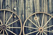 stock photo of wagon wheel  - A close up of two vintage wagon wheels lying up against a building - JPG