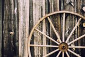 stock photo of wagon wheel  - A close up of a vintage wagon wheel lying up against a building partially in the frame - JPG