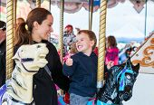 stock photo of funfair  - A happy mother and son are riding on a carousel together sharing a moment smiling at one another having fun at an amusement park - JPG