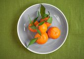 stock photo of clementine-orange  - Clementine tangerines with green leaves on green fabric in a grey bowl - JPG
