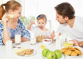 stock photo of breakfast  - Happy family mother father child baby daughter having breakfast at home - JPG