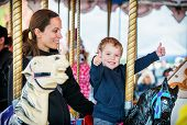 foto of amusement park rides  - A happy mother and son are riding on a carousel together smiling and having fun at an amusement park - JPG