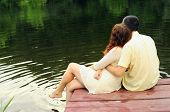 stock photo of pier a lake  - Couple of young lovers hugging on the pier of the lake  - JPG
