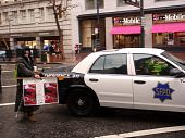 Protester Holds 'house Keys, Not Handcuff' Sign In Front Of Sfpd Car On Rainy Day