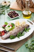 stock photo of greek food  - Mediterranean style organic roasted whole sea bass garnished with Greek salad - JPG