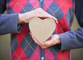 hands holding a valentine's day heart on a solid background