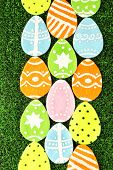 Colorful felt Easter eggs on grass close-up