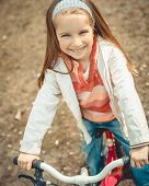 Little girl on a bicycle in summer park