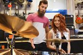 music, sale, people, musical instruments and entertainment concept - happy man and woman with drum kit at music store