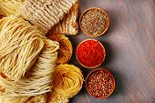 Different dry instant noodles with spices on wooden background
