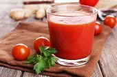 Glass of tomato juice with cherry tomatoes on wooden table close up
