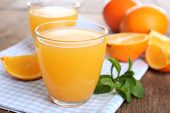 stock photo of orange-juice  - Glasses of orange juice with oranges on wooden table close up - JPG