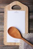 Cutting board with menu sheet of paper on rustic wooden planks background