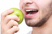 Man biting fresh green apple with healthy teeth isolated on white background