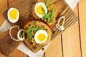 Sandwiches with green peas paste and boiled egg on cutting board with napkin on wooden planks background