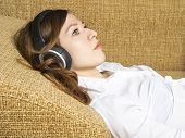 Girl lying on the couch and listening the music