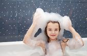 Little Girl Sitting In A Bath With Soap Suds On Her Head