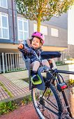 Little girl with helmet on head sitting in bike seat