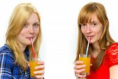 Two teenage girls drinking soft drinks