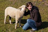 Woman Kneeling Beside A Small Lamb