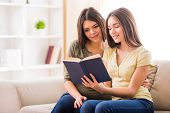 foto of daughter  - Beautiful mother and her cute teen daughter are reading a book together while sitting on sofa at home - JPG