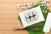 Sushi maki with cucumber and sakura branch over bamboo table