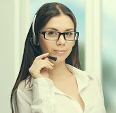 foto of telemarketing  - Young woman customer service representative or telemarketer wearing a headset at work at the office - JPG