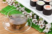 Green tea and sushi maki set on bamboo table