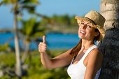 picture of caribbean  - Happy woman on tropical vacation doing success thumb up gesture and smiling - JPG