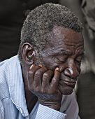 BOIS NEUS, HAITI - FEBRUARY 9, 2014:  Closeup of an elderly man sleeping (or praying) during a Christian church service in Haiti.
