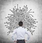 picture of microchips  - businessman looking to wall with drawing microchip - JPG