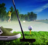 Golf Ball And Putter On Green Grass Of Course Against Young Man Driving Golf In Feild Use For Indivi