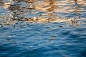 Ocean Water With Sunset Reflections. Intense Blue And Gold Colors