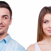 stock photo of heterosexual couple  - Beautiful young loving couple smiling and looking at each other while standing against white background - JPG
