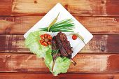 meat savory on wooden table: roast ribs on white plate with peppers lettuce tomato and chives