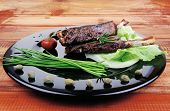 main course: barbecued ribs served with capers and chives . shallow dof