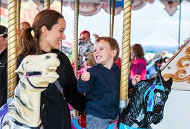 foto of carousel horse  - A happy mother and son are riding on a carousel together sharing a moment smiling at one another having fun at an amusement park - JPG