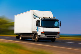 stock photo of moving van  - Small white truck on the road with motion blur effect - JPG