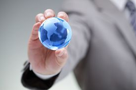 picture of fragile  - Business man holding a blue globe in his hand symbol for global business - JPG