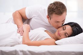 stock photo of early 20s  - Young couple lying in white bed early in the morning - JPG