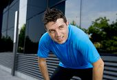 pic of breath taking  - young attractive man leaning exhausted after running session sweating taking a break to recover in urban street summer background - JPG