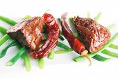 pic of veal  - served grilled beef veal fillet entrecote on a white plate with peppers and green peas on long plate isolated on white background - JPG