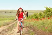 stock photo of preteens  - Preteen girl on bicycle with mother in spring field - JPG