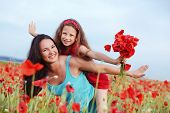 picture of 7-year-old  - Mother and her 7 years old preteen child playing in spring flower field - JPG