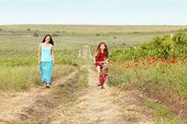 image of preteens  - Preteen girl on bicycle with mother in spring field - JPG