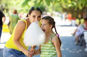 picture of candy cotton  - Child eats cotton candy with mom in city street - JPG