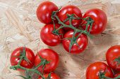pic of cluster  - Fresh tomatoes on a cluster over wooden table - JPG