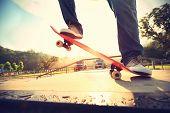 foto of skateboard  - skateboarder legs riding on skateboard at skatepark ramp - JPG
