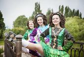 stock photo of wig  - Three young beautiful girls in irish dance dress and wig posing outdoor