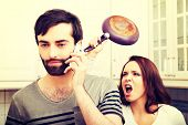 picture of adultery  - Young rage woman hitting her talking partner with frying pan - JPG